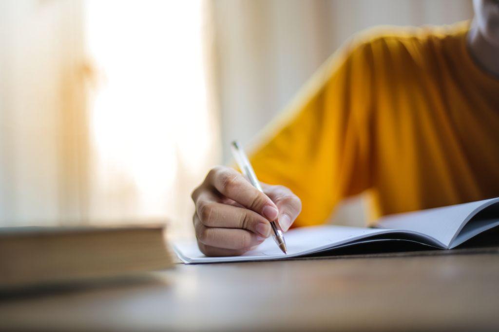 Ein Mensch schreibt in sein Notizheft.